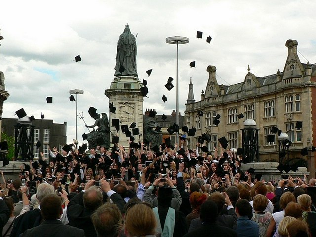 étudiants lançant leurs coiffes après l'obtention de leur diplôme