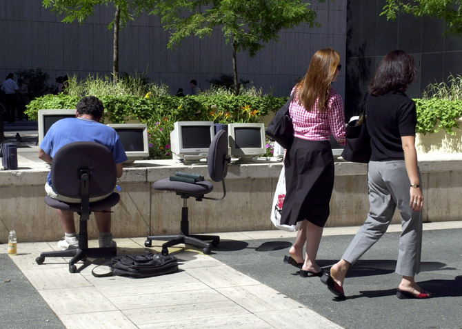 A homeless man sets up a computer store on the sidewalk