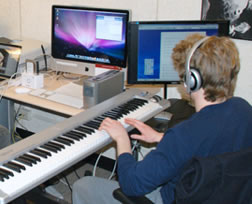 student composing music on keyboard