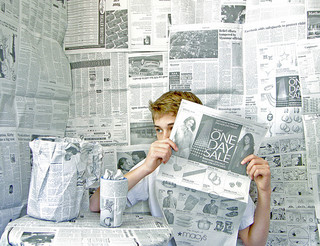 image of a boy reading a newspaper in a room constructed of newspapers