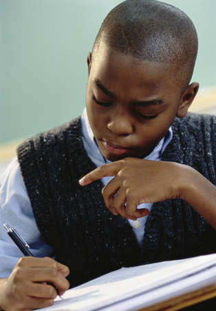 Male student frowning in concentration and writing in a notebook
