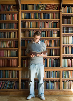 Man standing with back to bookshelves, holding and reading a book