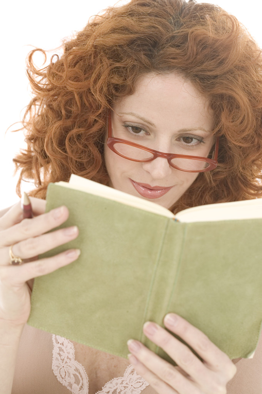 Red-headed woman wearing glasses and reading a book
