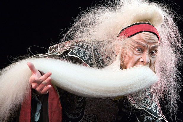 King Lear looking angry with right arm outstretched