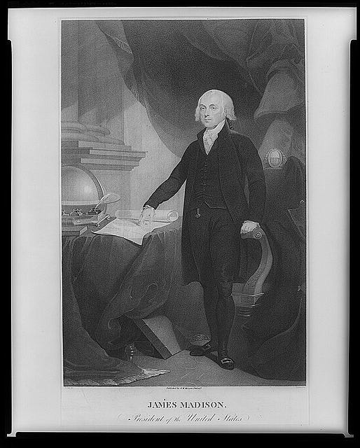 James Madison standing next to a table and pointing to a partially unrolled scroll of paper