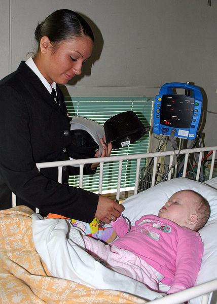Nurse with small child in hospital bed