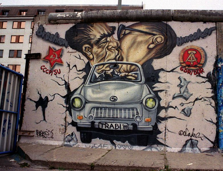 Mural on the Berlin Wall at the East Side Gallery featuring Leonid Brezhnev and Erich Honecker riding together in an East German Trabant (Spring 2002). Photo by Peter Rimar.