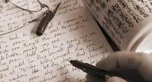 A hand holding a pen and writing on paper.