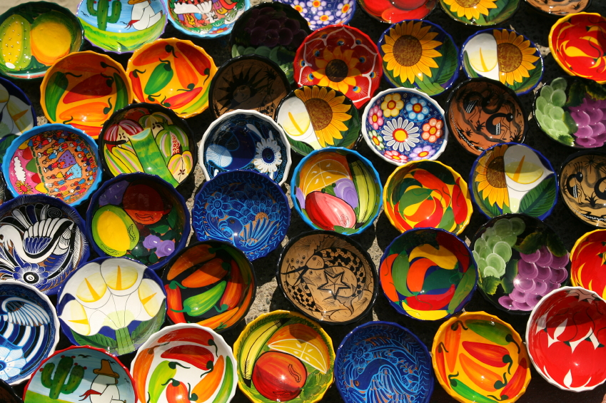A photo of brightly colored bowls with different designs painted on them.