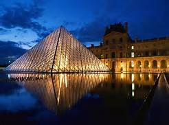 The glass pyramid in front of the Louvre museum in Paris, France at nighttime.