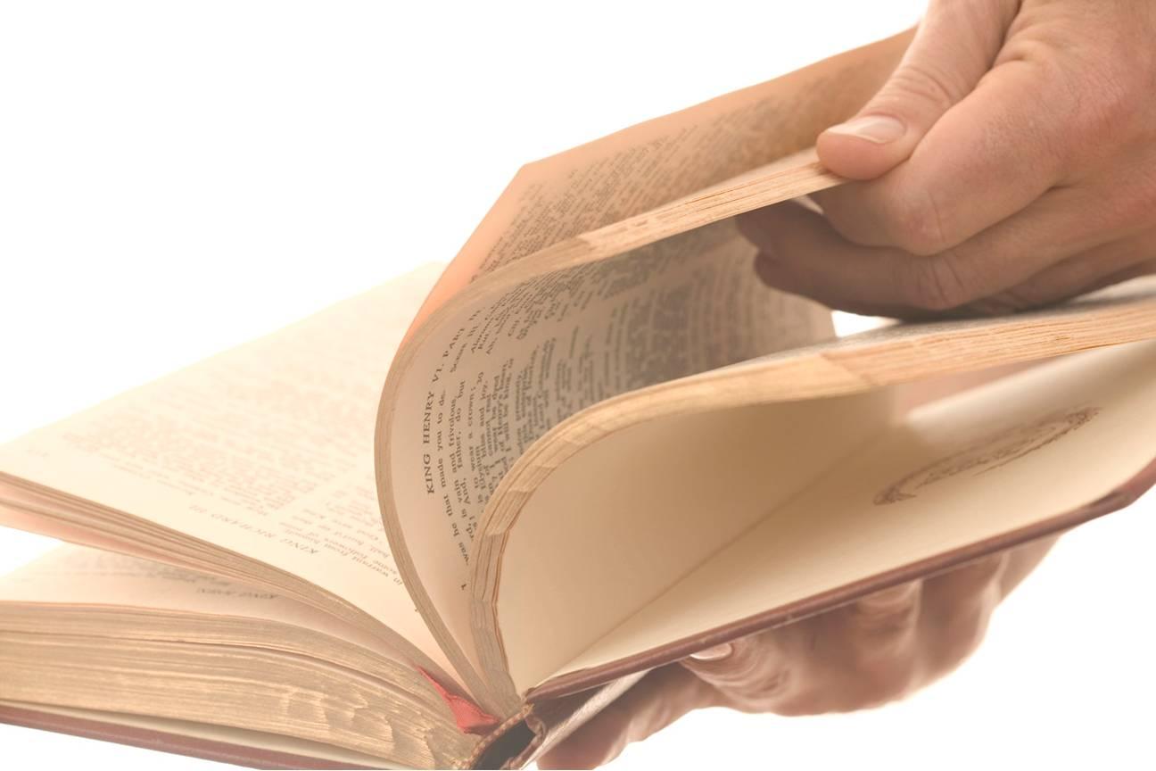 Hand flipping through an open book