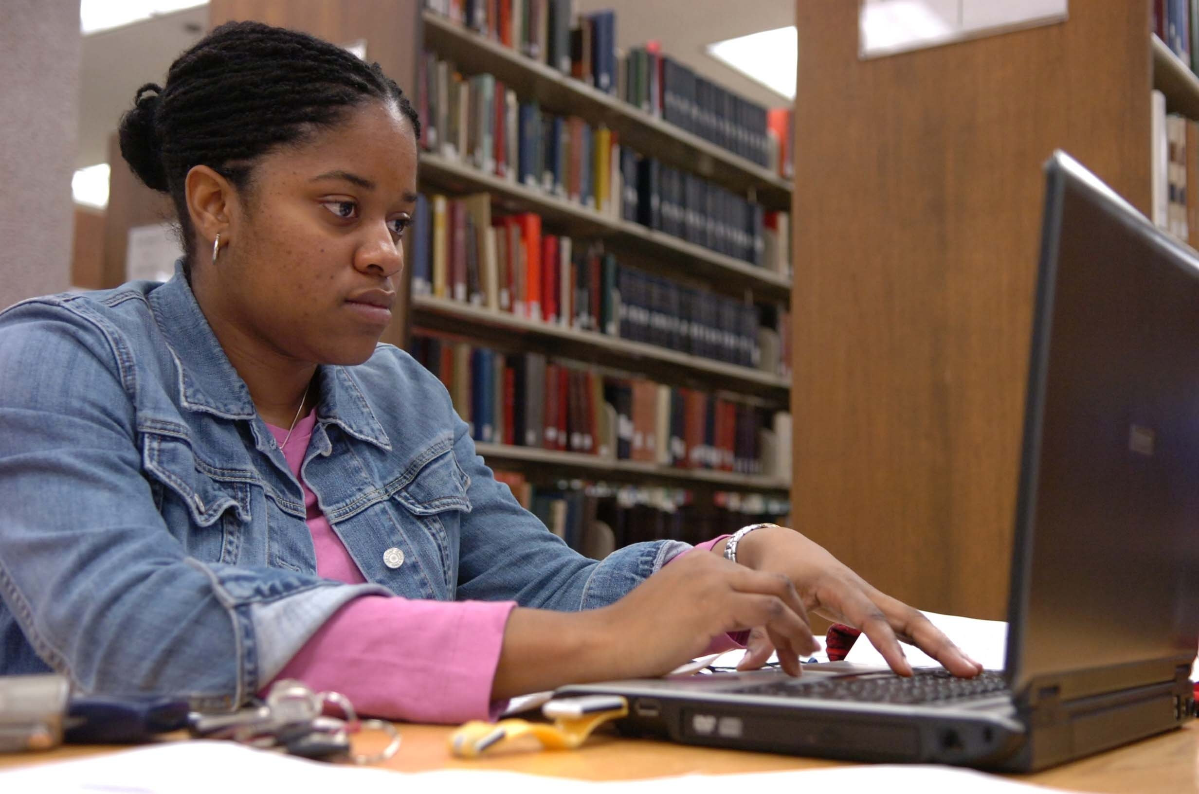 Student working at a laptop in the library