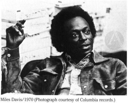 photo of Miles Davis with hand in air