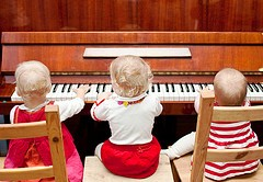 Piano Lesson - three young children playing the piano