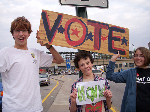 three children holding a vote sign