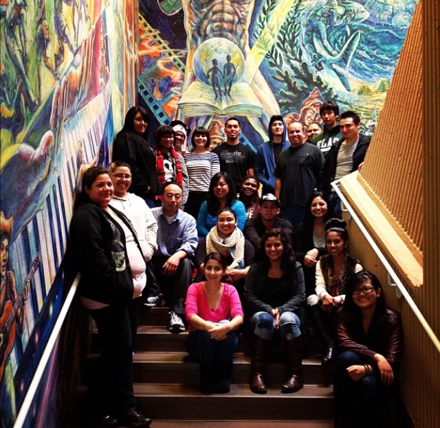 picture of students sitting by the library mural