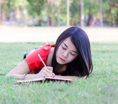woman writing in a notebook while lying in the grass