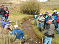 Group of people near a trail in the rangelands listening to someone speak.