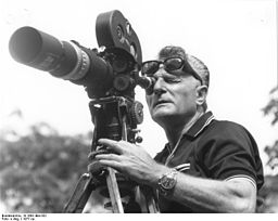 Photo of a man looking through the lens of an old-fashioined movie camera.