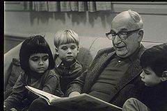 Photo of the H. A. Rey, the author of Curious George, reading his book to a group of children