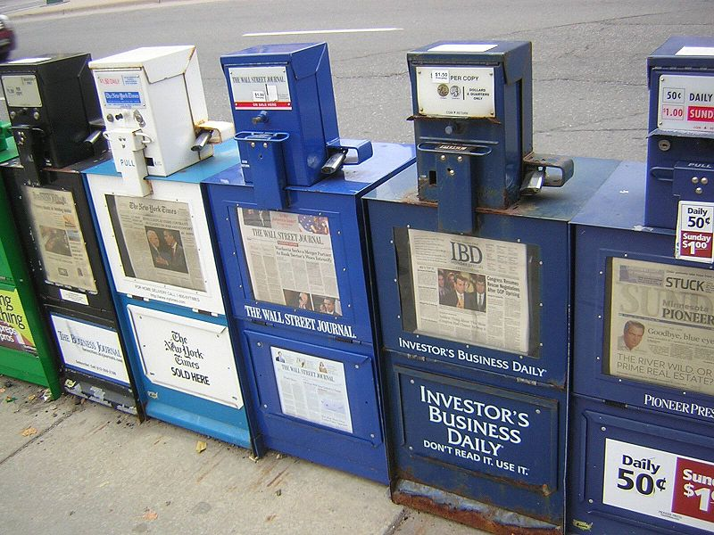 Photograph of newspaper boxes lined up along a street