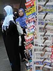 Photograph of two Muslim women near a newspaper stand