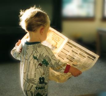 small child walking and reading a newspaper