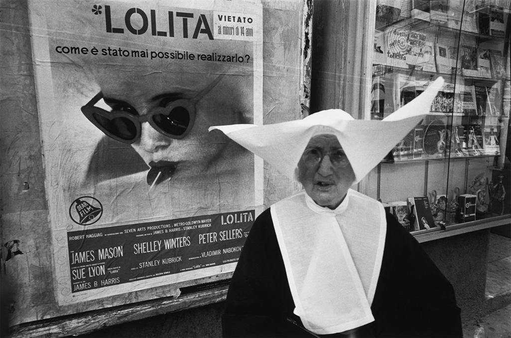 Nun in a habit and head covering in front of a movie poster for Lolita