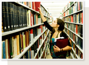 Picture of woman taking book of a library shelf.