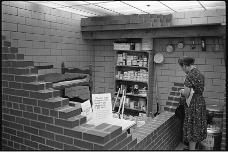 Woman in bomb shelter which is stocked with food and other supplies; bunk bed in corner