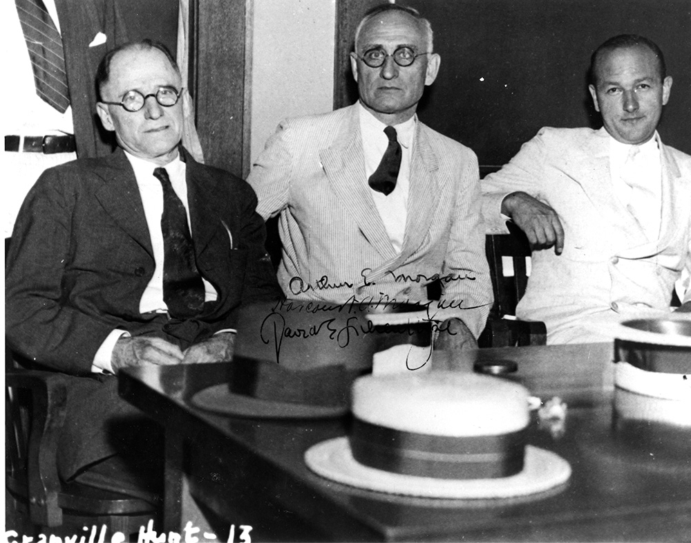 black and white photograph of the First TVA Board with their signatures in the middle of the photograph. The three men are sitting at a table.