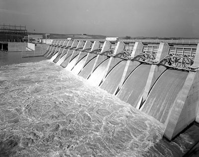 black and white photograph of A TVA dam with water flowing into and filling up the reservoir