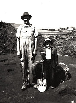 Black and white photograph of two TVA Workers, man and son possibly, smiling and holding a shovel.