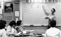 Serge Ainsa standing in front of whiteboard teaching students sitting at tables.