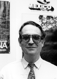 Smiling photo of Serge Ainsa in sunglasses standing in front of a Mexican restaurant.