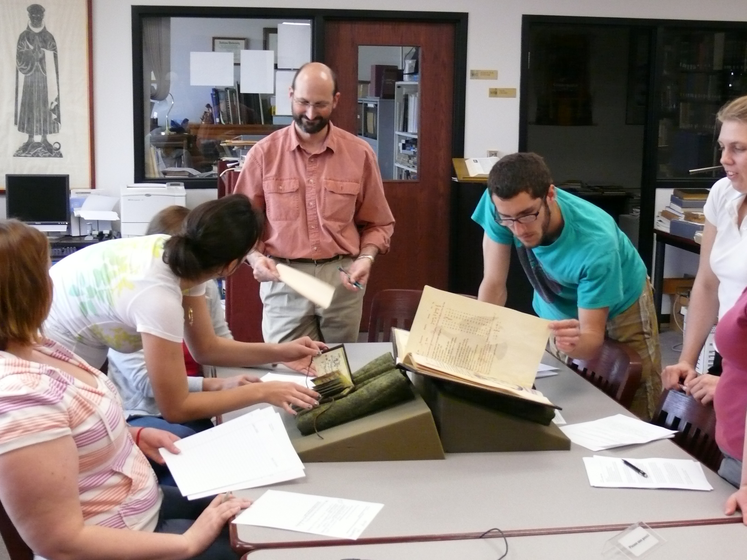 Instructor answering questions of students consulting rare books