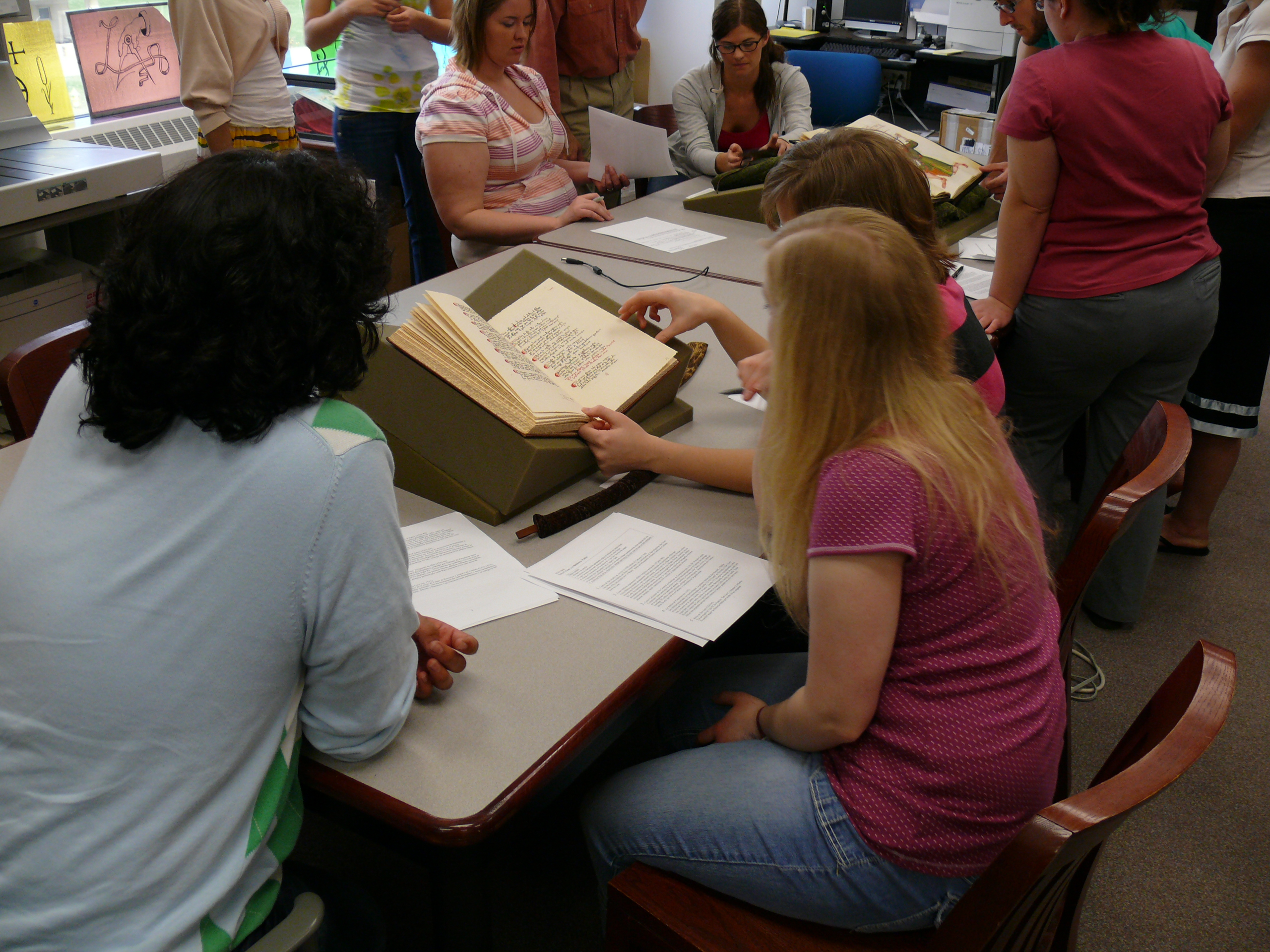 Students consulting rare books during a course visit