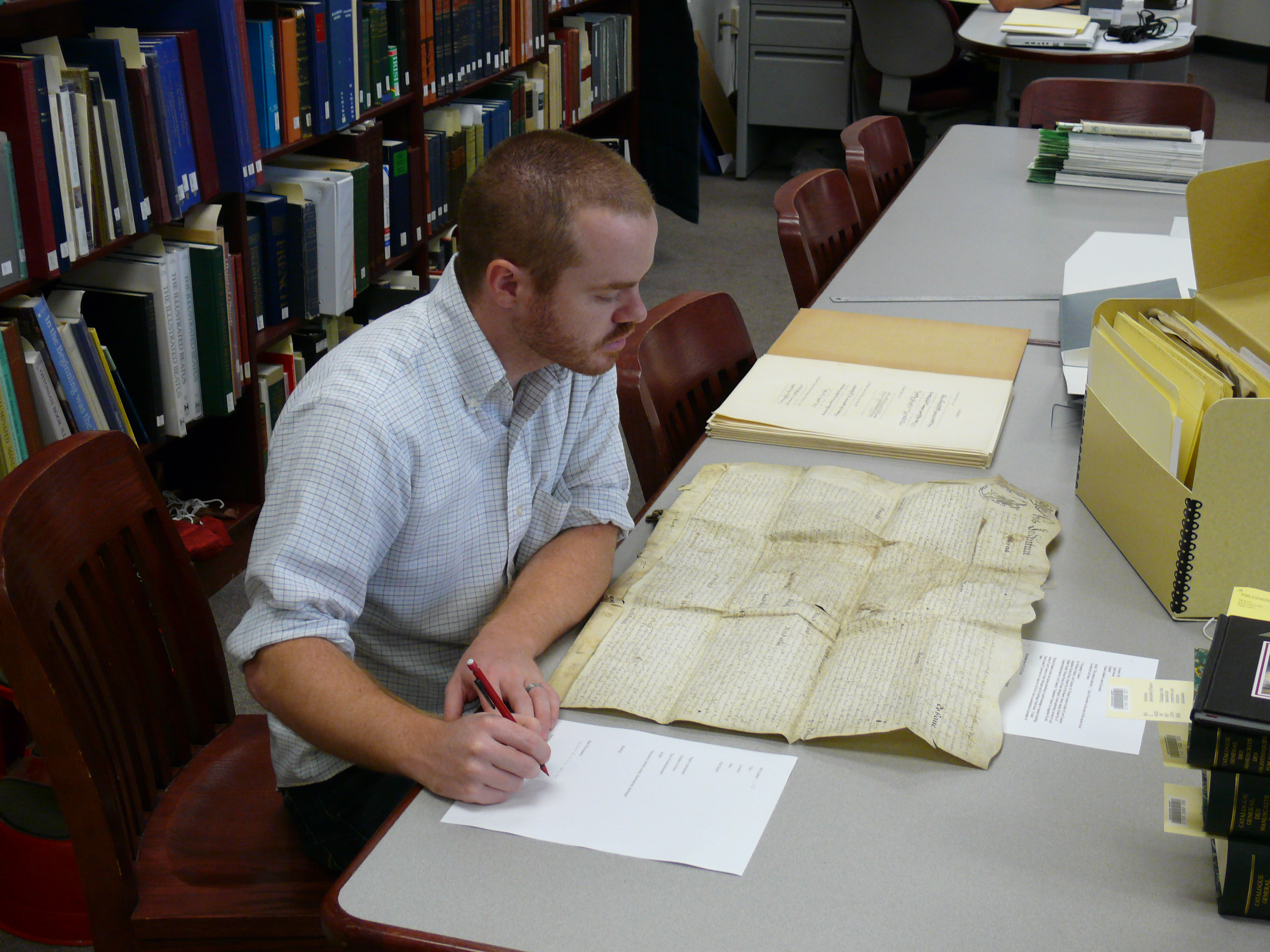 Researcher taking notes on a manuscript