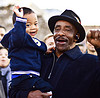 man holding his grandson at a rally