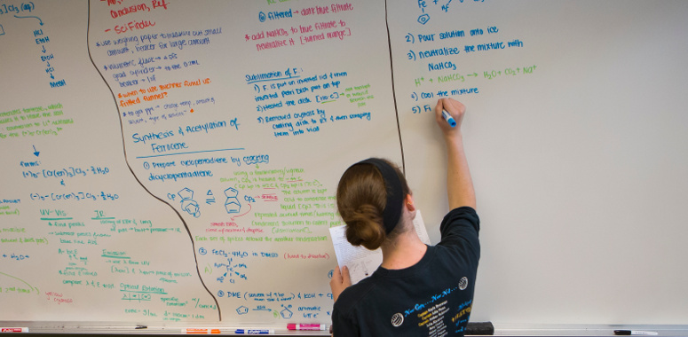 Furman Student Writing on White Board in the Sanders Science Library