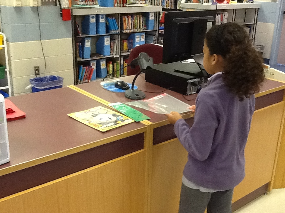 student checking out book