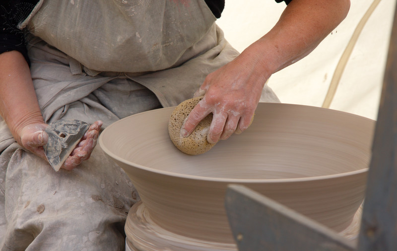 A Potter is Smoothing a Bowl on the Potter's Wheel.