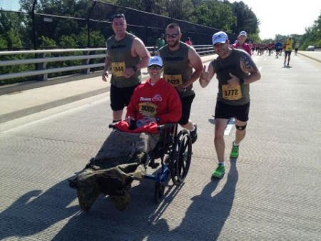 Staff Sgt. Jack Blevins in wheelchair running with friends