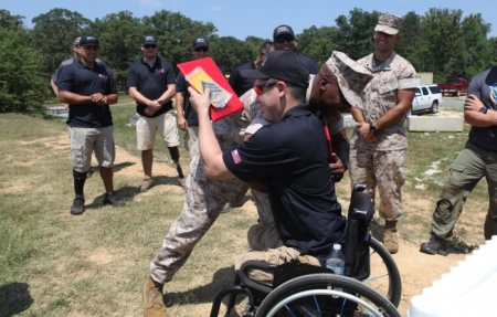 Sgt Ivan Sears in wheelchair receives promotion and embrace from WWR sergeant major