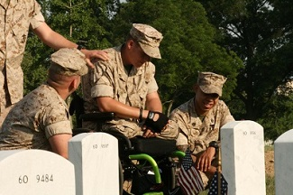 Marine in wheelchair and Marines visiting graveside