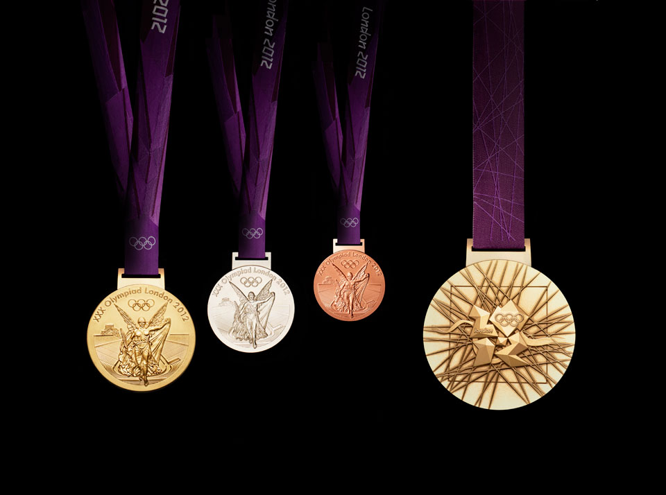 In front of a purple velvet drape hang (from left) the front of the 2012 gold, silver, and bronze medals. On the right is the back of the gold medal.