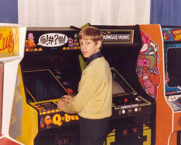 A boy stands in front of a Q-bert arcade console, his hands are on the controls but he has turned his head to face the camera. Other vintage aracade consoles including Jungle Hunt, can be seen in the background.