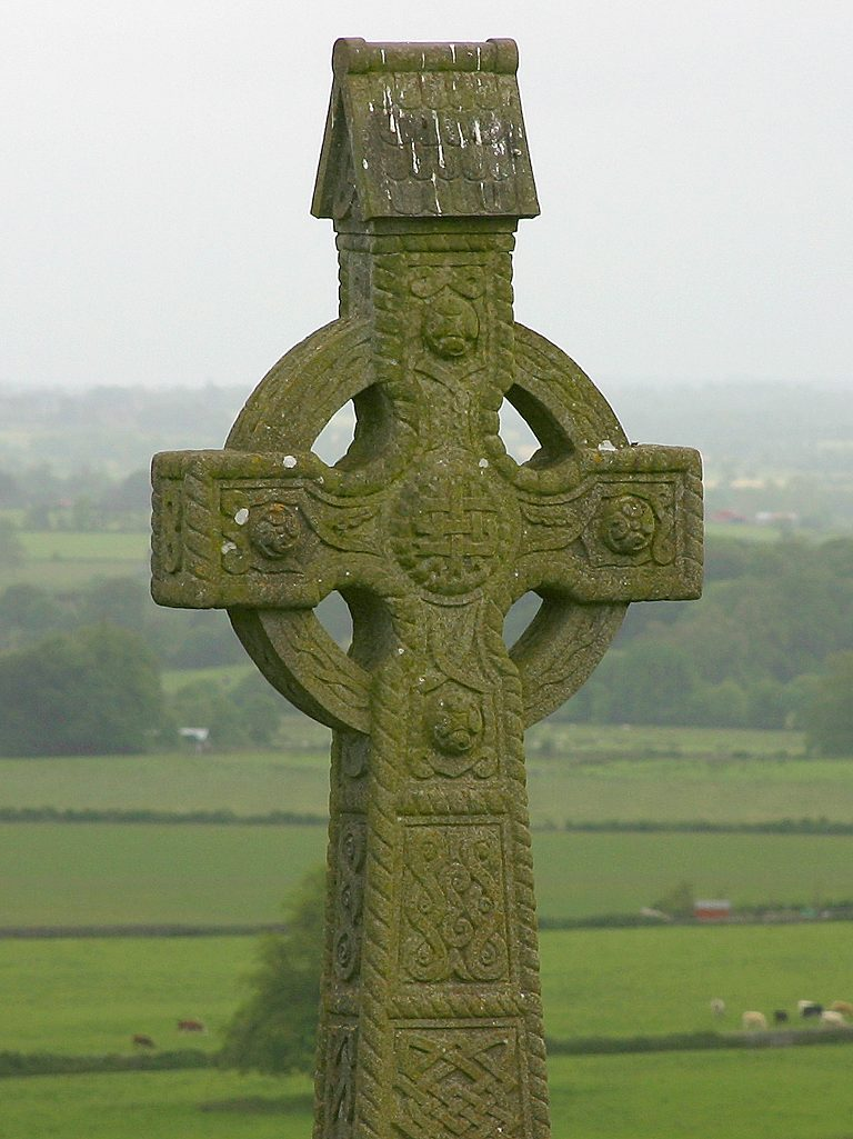 An old stone Celtic cross is seen before a green landscape