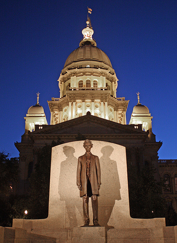 Illinois State Capitol dome illuminated at night with Lincoln statue in foreground