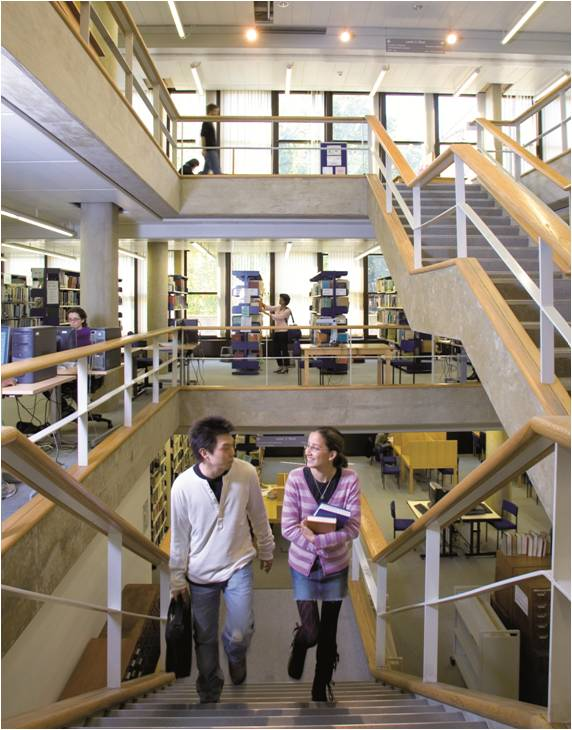 image of the central staircase at the IOE Library with two students walking up from Level 3 to Level 4